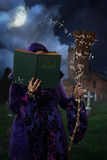 Book Of Magic Spells. Woman wearing purple cloak in graveyard with book of magic spells and broomstick Royalty Free Stock Image
