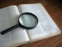 Book and magnifying glass Stock Images