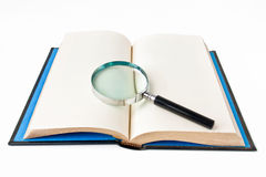 Book and magnifying glass. Book with magnifying glass on white background Stock Photos