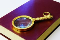 Book and magnifying glass Royalty Free Stock Images