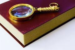 Book and magnifying glass Stock Photos