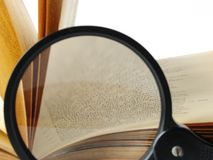 Book with magnifying glass Stock Images