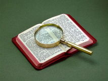 Book and Magnifying Glass. An old magnifying glass lying on a small, opened edition of the New Testament Stock Images