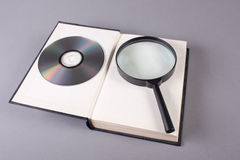 Book with magnifying glass and compact disk Royalty Free Stock Images