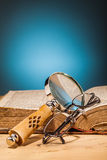 Book  magnifying glass  and  glasses on wooden table Stock Image