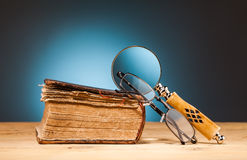 Book  magnifying glass  and  glasses on wooden table Stock Images