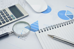 Book, magnifying glass, pen and calculator on financial chart an Stock Photography