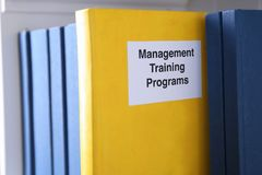 Book of MANAGEMENT TRAINING PROGRAMS. On shelf Royalty Free Stock Image
