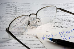 Book, math, glasses, hadwritten notes. Study or research concept - book with heavy math, reading glasses and handwritten notes Stock Image