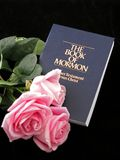 Book of mormon and roses. The book or mormon with decorative pink roses; isolated on black background Royalty Free Stock Photos