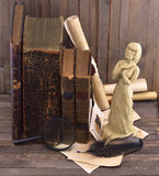 Book muse. Old books with clay figurine of girl on the wooden background Royalty Free Stock Photo