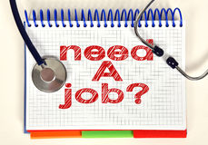 Book with need a job. Open book with need a job and stethoscope on tab Stock Images