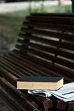 Book and newspaper. A book and a newspaper on a bench Royalty Free Stock Image