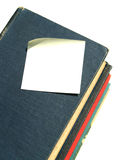 Book Note 9. Blank note paper  on old red, green, black, blue hardcover books Stock Photo