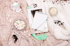 A book, a notebook, a candle in a glass candlestick, parvarda, peanuts in sugar, a statuette of an angel made of white plaster, a. Wristwatch on a soft, beige royalty free stock image