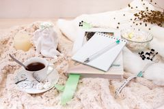A book, a notebook, a candle in a glass candlestick, parvarda, peanuts in sugar, a statuette of an angel made of white plaster, a. Wristwatch on a soft, beige stock photo
