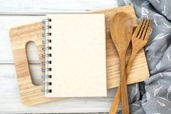 A book notepad paper on chopping cutting board and tablecloth on. Book notepad paper on chopping cutting board and tablecloth on white table , recipes food for stock photography