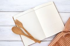 Book notepad paper and tablecloth with wooden fork and spoon on. A book notepad paper and tablecloth with wooden fork and spoon on white table , recipes food for royalty free stock photos