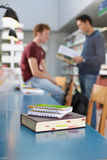 Book and notepads on desk in library Stock Image