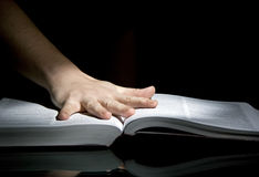 Book and open hand. An open hand resting on a book, black background, selective spotlight Stock Photos