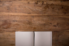 Book opened blank on dark wooden background with copyspace, top- Royalty Free Stock Images