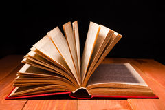 Book opened in library on wooden shelf. Education background with copy space for text Royalty Free Stock Images