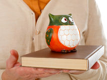 Book & owl symbol of wisdom. Close up picture of an elderly woman holding a book and an owl as the symbol of wisdom Royalty Free Stock Photo