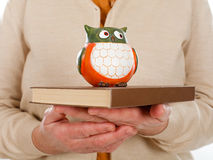 Book & owl symbol of wisdom. Close up picture of an elderly woman holding a book and an owl as the symbol of wisdom Stock Image