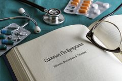 Book page medicine of common flu symptoms in schools, businesses and travelers, current metaphorical image. Horizontal composition royalty free stock photos