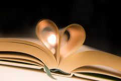 Book pages folded into heart. Love sign with romantic candles stock images