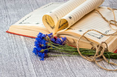 Book pages folded into a heart and a flower of bouquet cornflowe Royalty Free Stock Photo