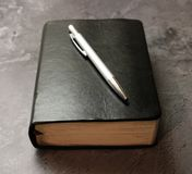 A book and a pen. With marble backgorund royalty free stock photography