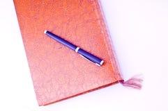 Book and pen Stock Photos