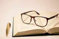Book and pen. On the desk with glasses Stock Photography