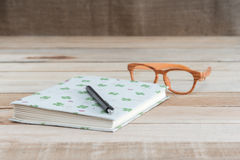 Book and pen,eyeglass on wood table Stock Photo