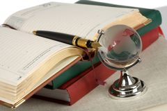 Book, pen and glass globe royalty free stock images