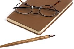 Book with pen and glasses. A writting book with glasses on top and an old pen in front Stock Photos