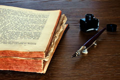 Book with a pen and ink. An open book with a pen and ink on top Royalty Free Stock Image