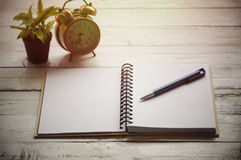 Book and pen on table with plant Royalty Free Stock Image