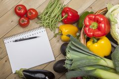 Book with pen and vegetables Stock Images