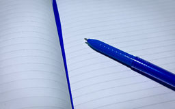 Book and pen. A white book and a blue pen Royalty Free Stock Images
