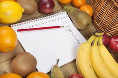 Book and pencil admist fruits Royalty Free Stock Photography