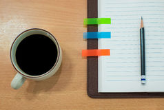 Notebook,pencil and coffee on wooden table. Top view Royalty Free Stock Image