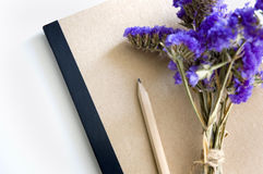 Book and pencil. Natural color book and pencil with purple flowers Stock Images