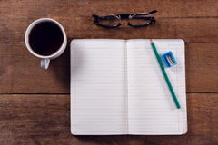 Book, pencil, sharpener, spectacles and black coffee on wooden table. Overhead view of book, pencil, sharpener, spectacles and black coffee on wooden table Royalty Free Stock Images