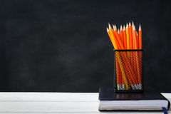 Book and pencil on white table black board background. With study and education concept.selective focus Royalty Free Stock Photos