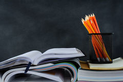 Book and pencil on white table black board background Royalty Free Stock Image