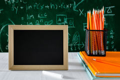 Book and pencil on white table black board background with study Stock Photos