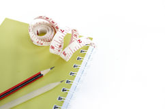 Book and pencils with tape measuring on white Stock Images