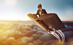 Person flying in a book over the clouds. A book with a person in pilot googles is flying over the clouds. Scenic sunset atmosphere Stock Photography